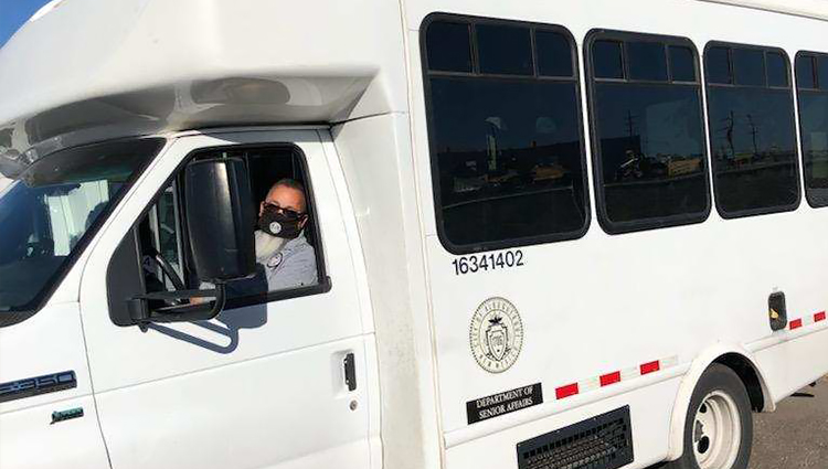 A Masked Senior Affairs Services Staff Member Driving a City Van