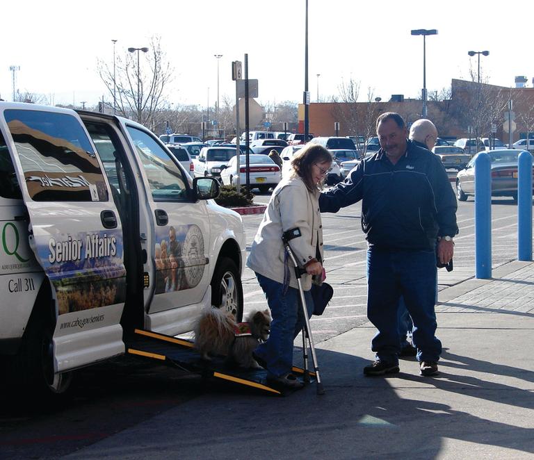 Man Helping Woman Out Of Van