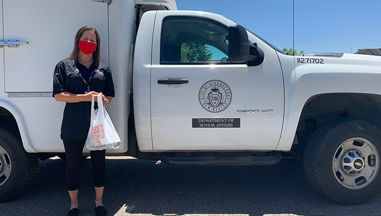 Masked Volunteer Standing with Food in Bag Next to City Truck