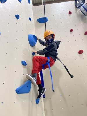 Child with mask climbing rockwall