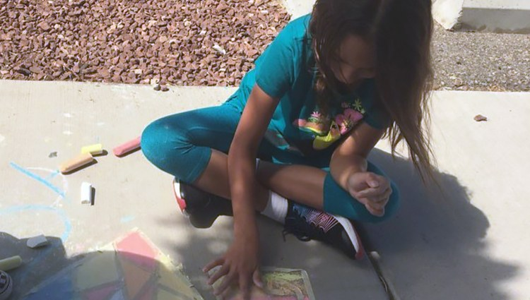 Young Girl Playing with Chalk on a Sidewalk