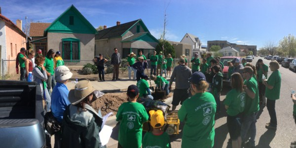 Volunteers planting a tree in a neighborhood.