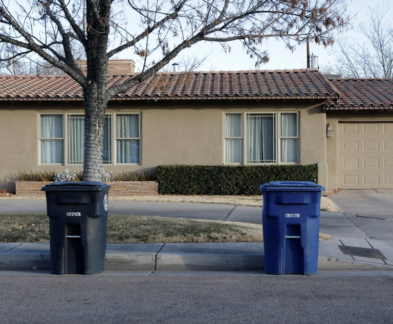 A recycling cart and a trash cart spaced at least five feet apart.