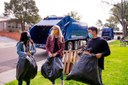People Carrying Bags of Trash in Park
