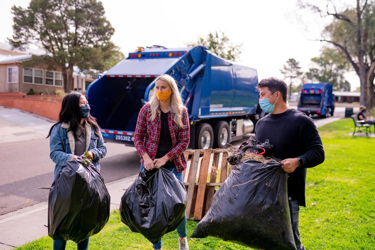 Three people carrying bags of trash in a park.