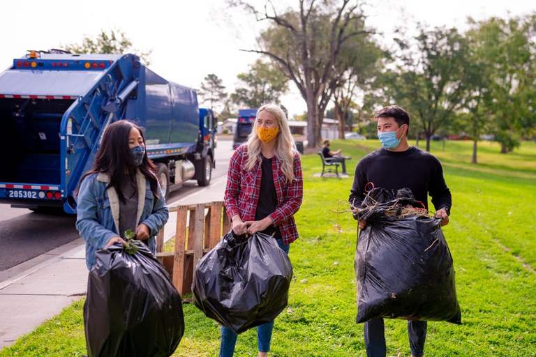 Three young people in masks picking up trash in a park.