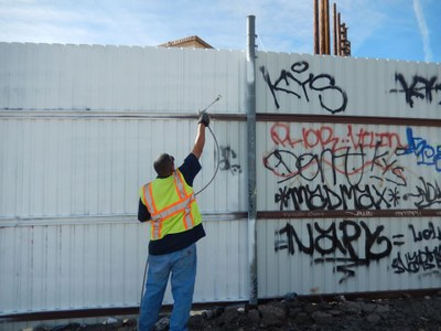 An image of an employee cleaning up graffiti.