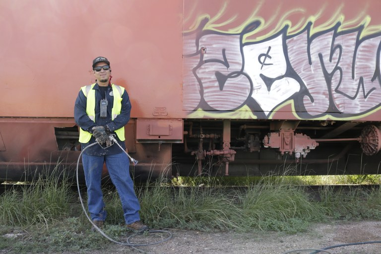 A Solid Waste Department Employee standing next to some graffiti.
