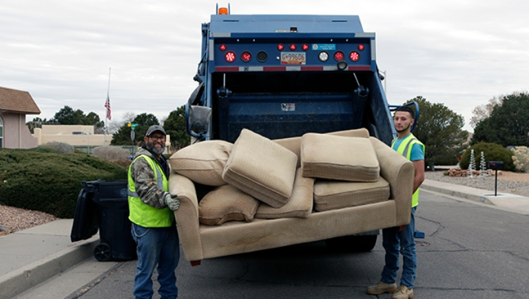 Two SWMD employees placing an old couch into a trash truck.
