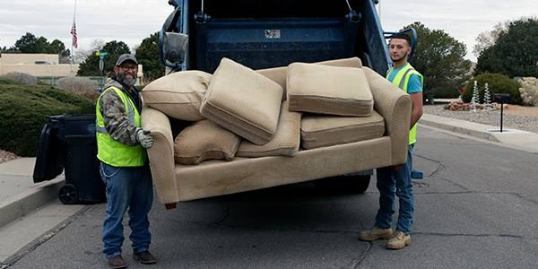 Solid Waste Department employees loading an old couch into a collect truck.