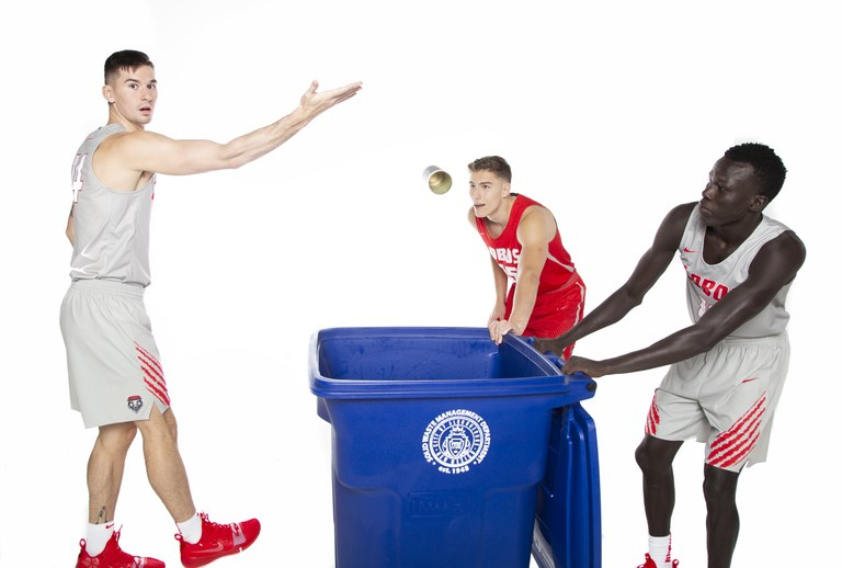 UNM Lobo Basketball Players throwing cans in a recycle bin.