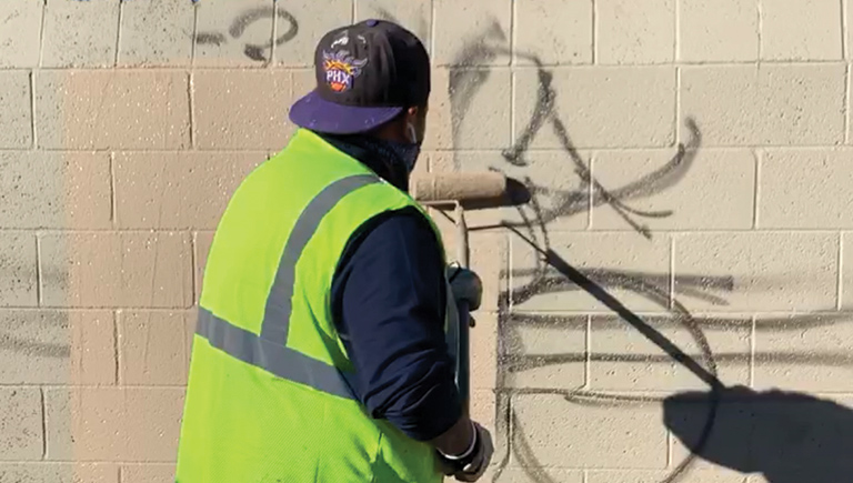 A worker cleaning graffiti from a wall