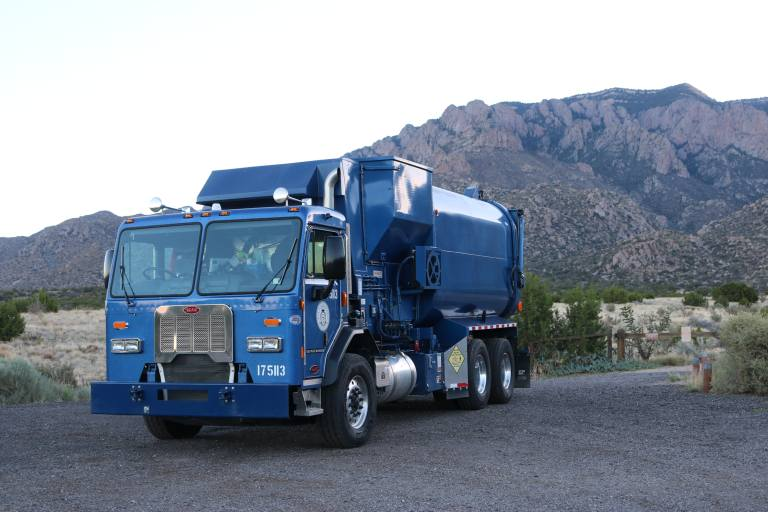 A trash truck in front of the Sandia Mountains