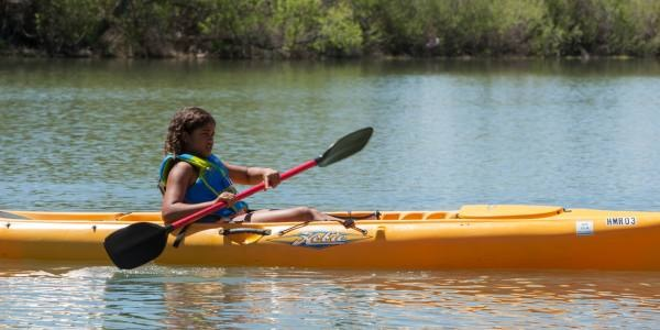 A child kayaking along the Rio Grande.