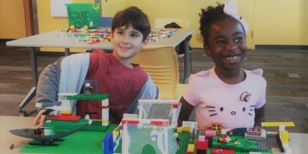 Two children playing with lego toys at a library.