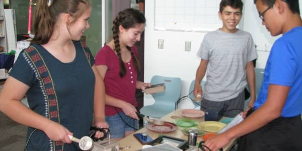 Four youth participants using science equipment.