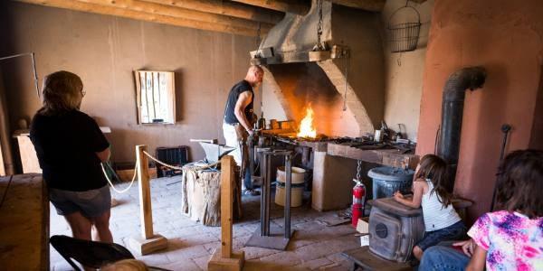 Visitors watching a blacksmith at Casa San Ysidro.