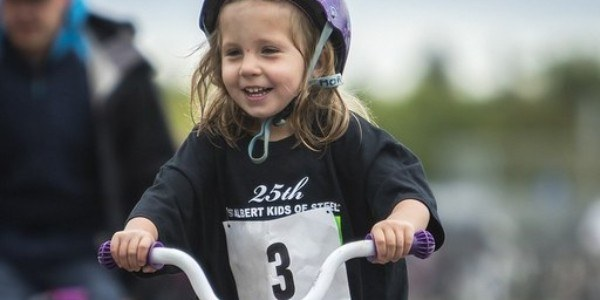 A young girl wearing a helmet and riding on a bicycle.