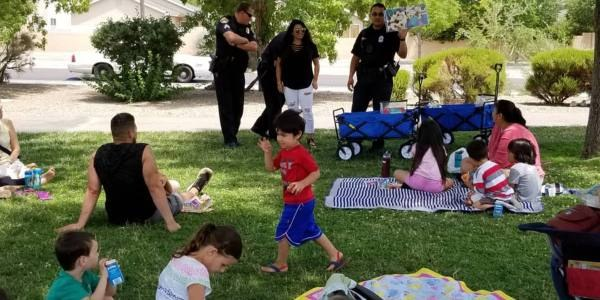 Police officers reading to children in a park.