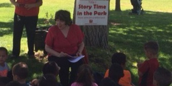 An image of a teacher reading to children in a park.