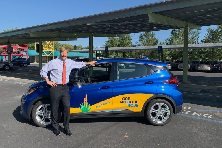 Mayor Keller leaning on one of the City of Albuquerque's electric vehicles.