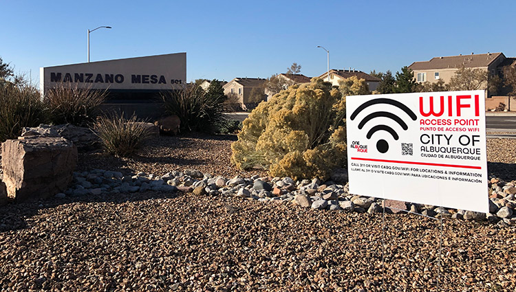 A jpg of a WiFi in Neighborhoods yard sign and the Manzano Mesa sign with a neighborhood in the background.