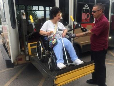 Image of a Sun Van driver assisting a passenger in a wheelchair board a Sun Van.
