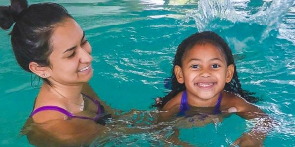 A mother and a daughter in swim lessons.