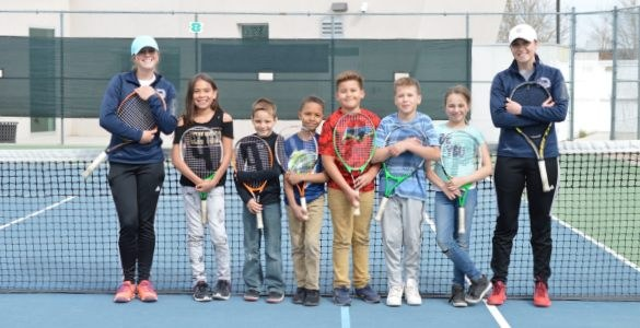 Children in tennis lessons with their instructors.