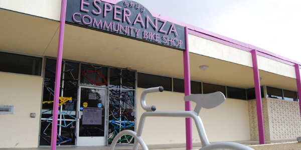 A photo of a child getting their bike worked on at Esperanza Bike Shop.